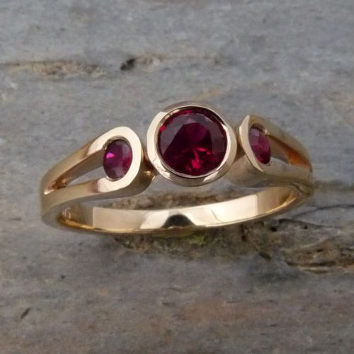 118RGR Ring in 18ct Yellow Gold loop shank featuring 3 round faceted Rubies in centre bezel setting and channel set into the shanks