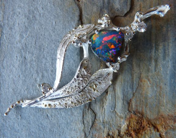 Australian Gum Leaf Design Pendant in 925 Ag Sterling Silver with gold dust soldered on top of the leaves, embracing a solid Australian Opal in striking colour play
