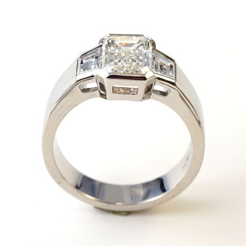 Custom-Design: Ring in 950Pt Platinum with side openings, featuring an Emerald cut 1.51ct Diamond and Trapezoid pair 0.54ct