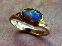 Ring non-symmetric sculptured shank in 18 ct yellow gold bezel setting around oval Australian opal
